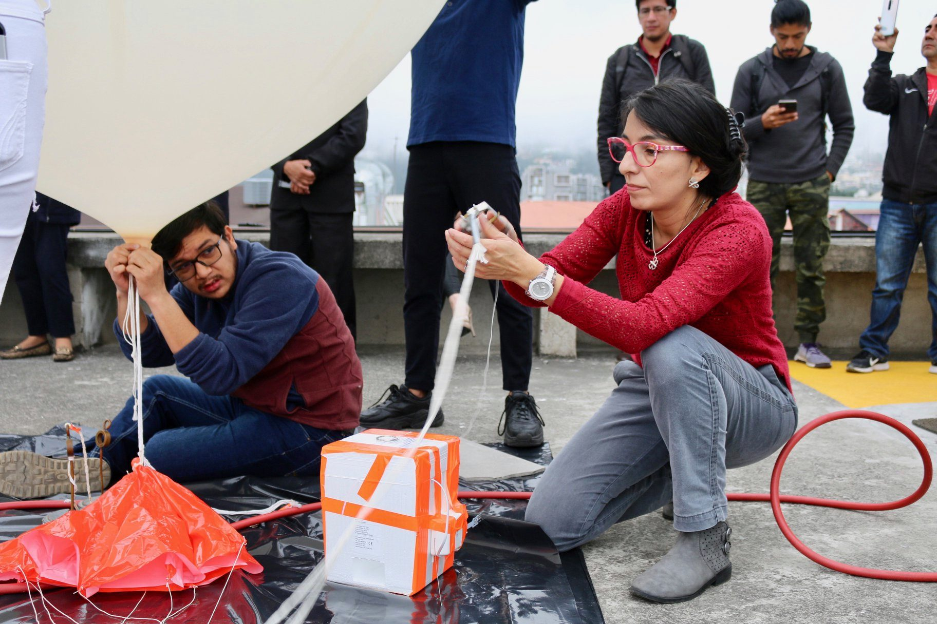 Preparations to launch the first ozonesonde of the ECHOZ project from Universidad San Francisco de Quito on 6 March 2020. On the picture, M. Cazorla and E. Herrera complete balloon filling with helium and anchoring ozonesonde-radiosonde package to platform prior to launching.
